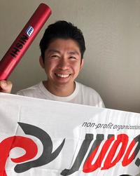 「JUDOs」のフラッグを手にする鈴木利一事務局長