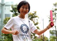 新エンブレムのTシャツを着てバトンを持つ東京五輪・パラリンピック大会組織委員会の小野日子スポークスパーソン
