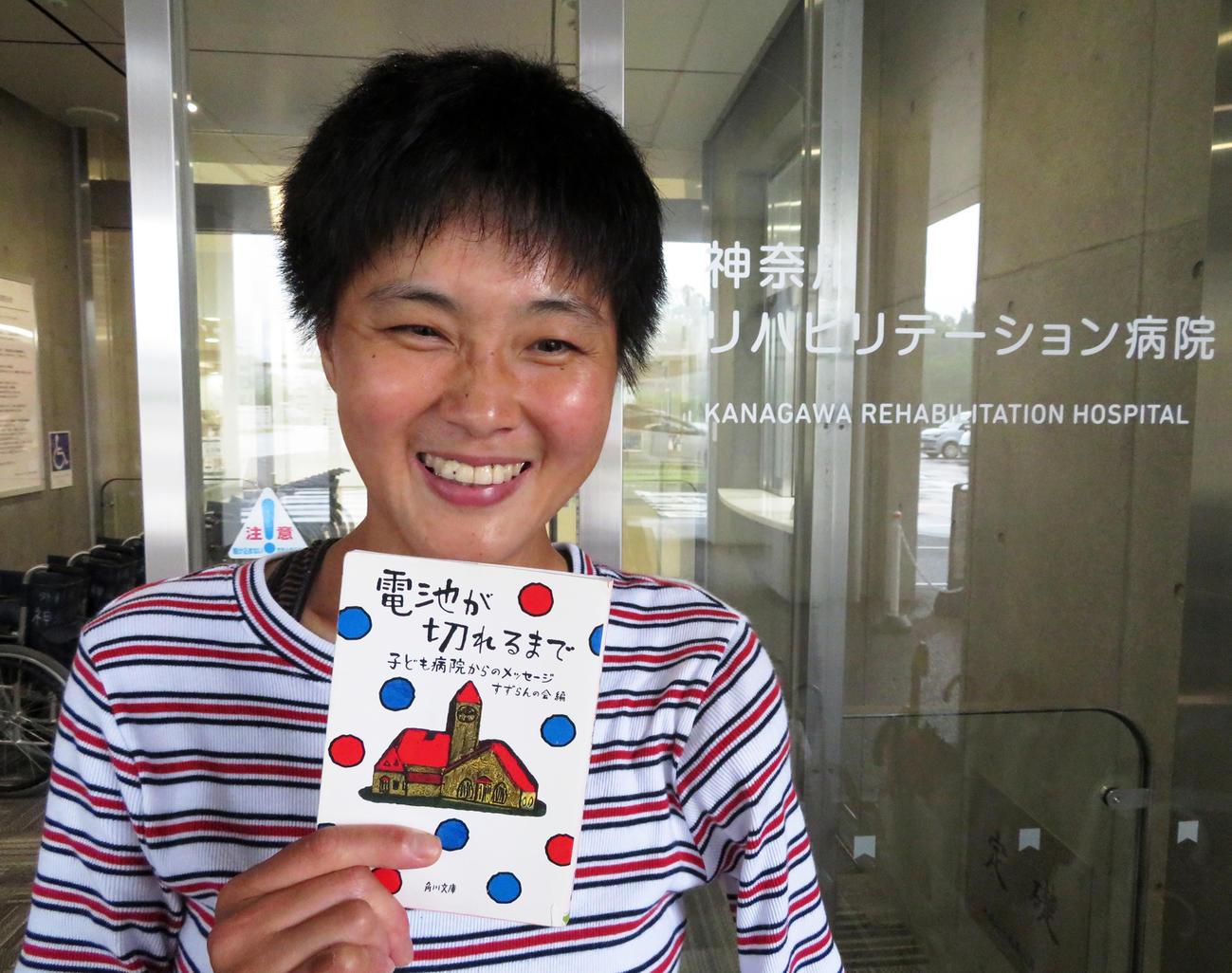 鹿沼由理恵は勤務先の神奈川リハビリテーション病院で愛読書「電池が切れるまで」を手に笑顔を見せる
