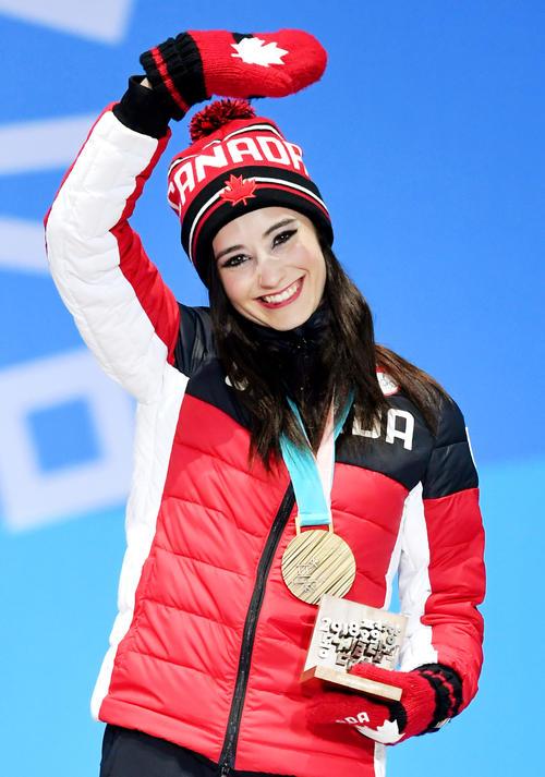 平昌冬季五輪のフィギュアスケート女子で獲得した銅メダルを胸に歓声に応えるカナダのケイトリン・オズモンド(共同)