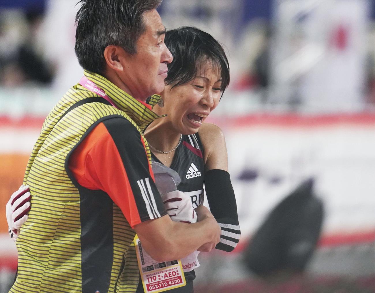 2位でゴールし、ワコールの永山忠幸監督(左)に支えられる安藤友香(共同)