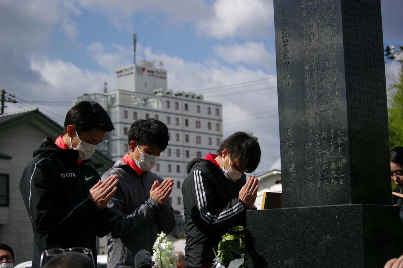 円谷幸吉さんの墓前で手を合わせる東京五輪マラソン男子代表の服部(左端)ら(撮影・奥岡幹浩)