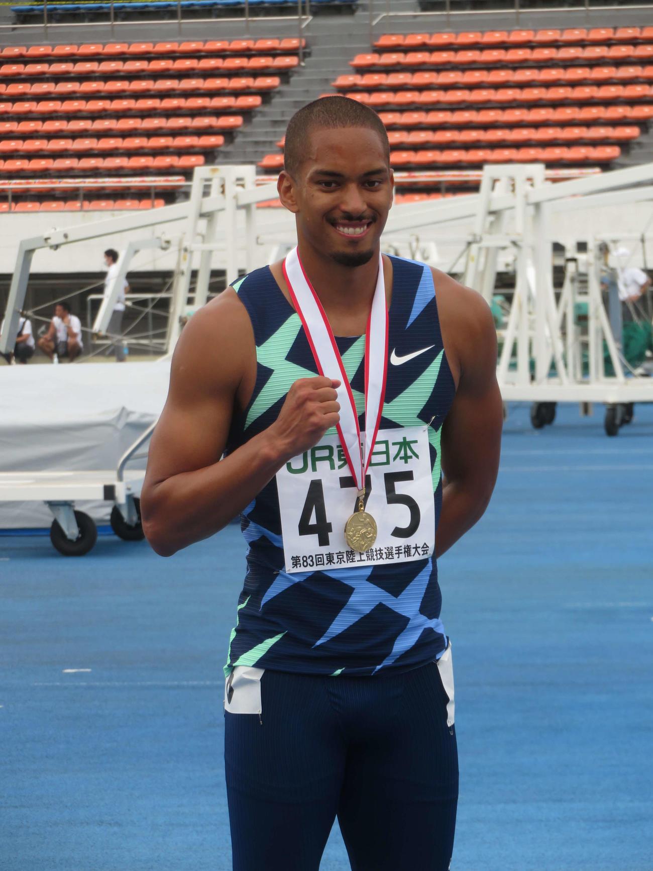 男子100メートル優勝のの金メダルを首にかけ、笑顔のケンブリッジ(撮影・上田悠太)
