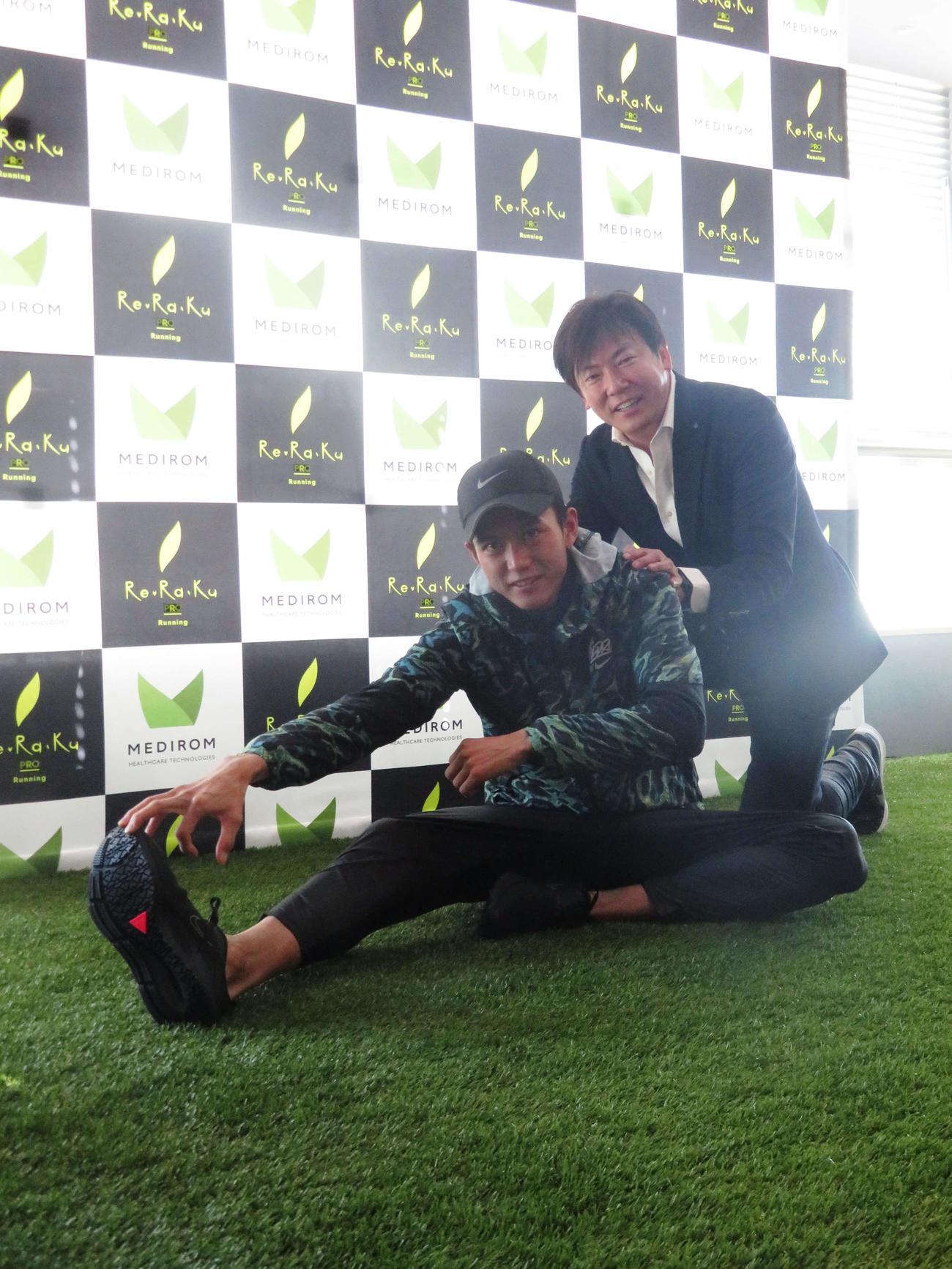 報道陣のリクエストに応じ、大迫傑(左)の体を押すメディロムの江口康二代表取締役(撮影・上田悠太)