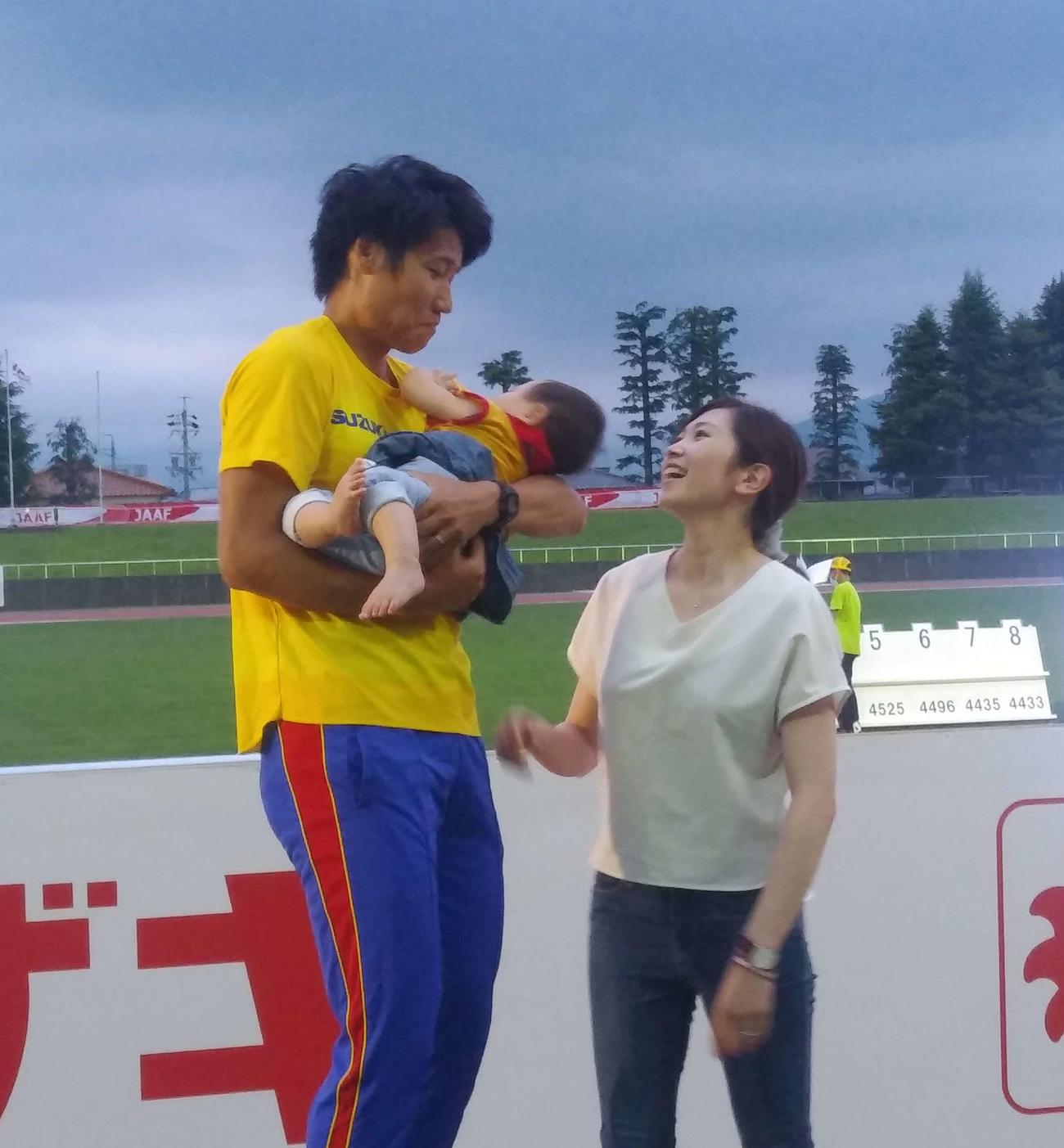 男子10種競技の全種目を終え、長女翠杏ちゃんを抱く、中村明彦(左)と妻紗綾さん(撮影・上田悠太)