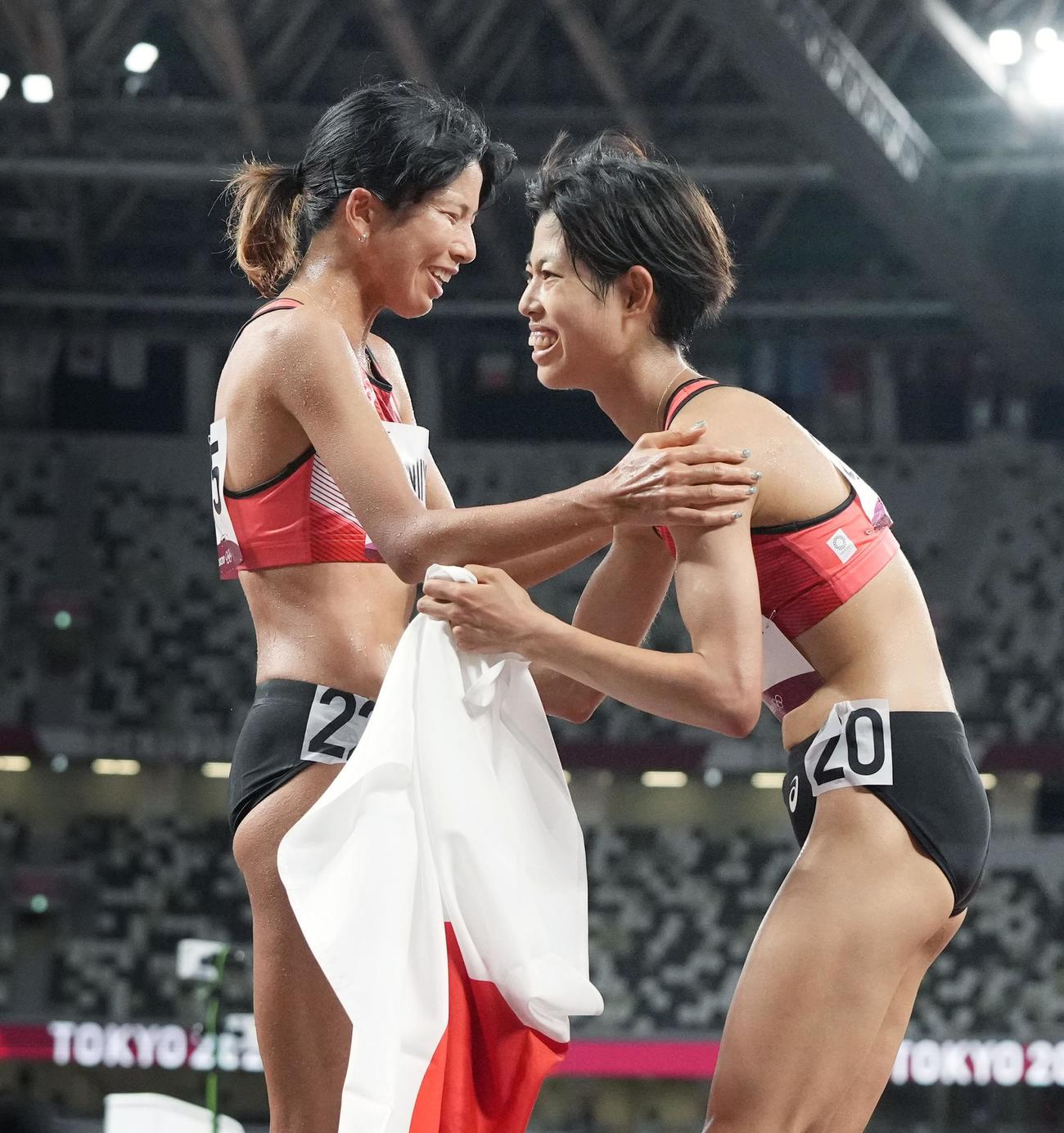 女子1万メートルで7位入賞を果たし新谷(左)と健闘をたたえ合う広中(共同)