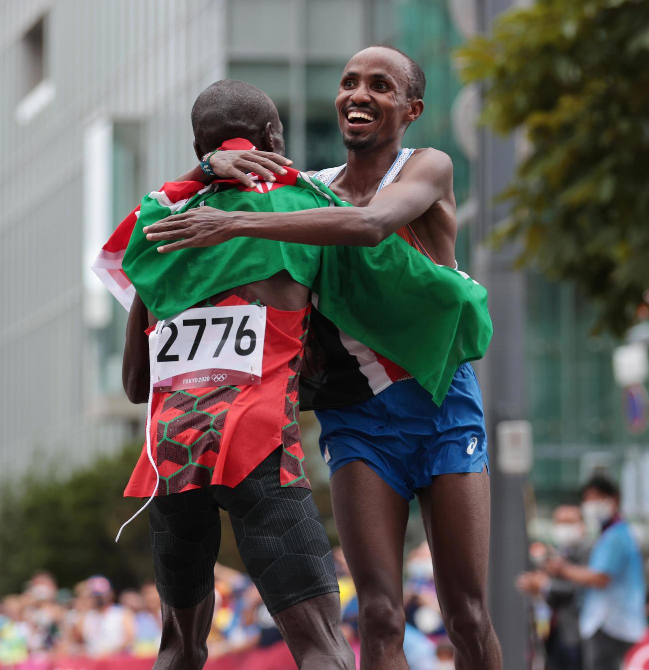 陸上男子マラソン 優勝したケニアのキプチョゲ(左)と抱き合って喜ぶ2位のオランダのナゲーエ(代表撮影)