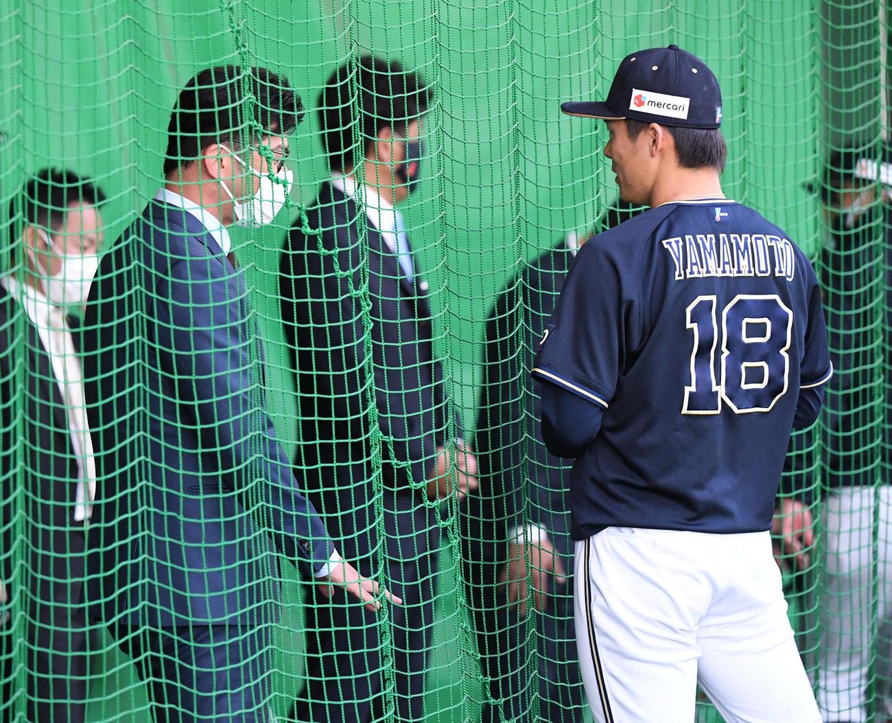 ブルペンで投球練習を終えたオリックス山本(右)は侍ジャパン建山コーチと話す。中央は稲葉監督(撮影・前岡正明)