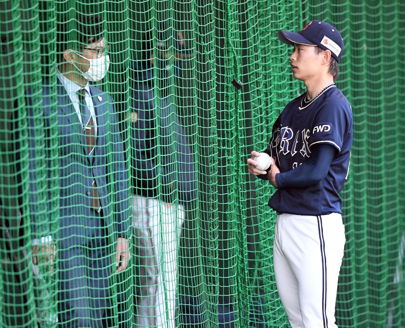 ブルペンで投球練習を終えたオリックス山岡(右)は侍ジャパン建山コーチと話す(撮影・前岡正明)