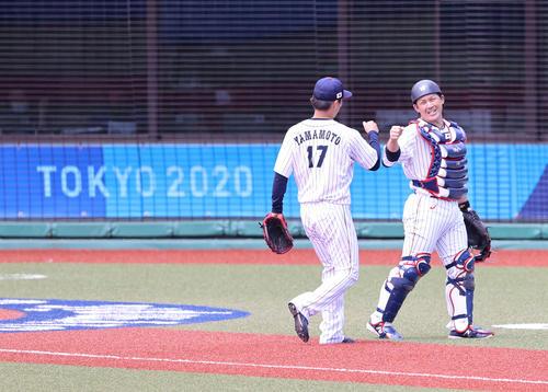 日本対ドミニカ共和国 1回表を無失点で終え、山本(左)とグータッチをかわす甲斐(撮影・河野匠)