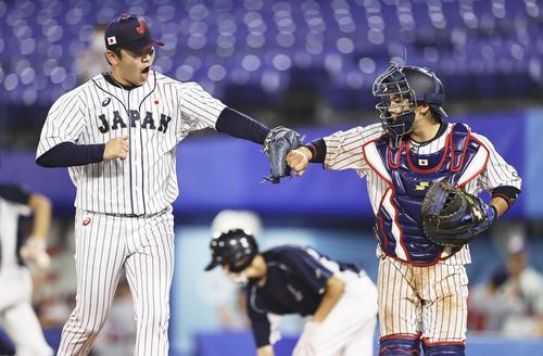 8回、無失点で終え、捕手梅野とタッチを交わす山崎(共同)