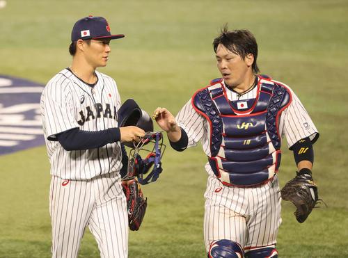 日本対韓国 4回表を終え、好守の甲斐(右)にマスクを渡す山本(撮影・河野匠)