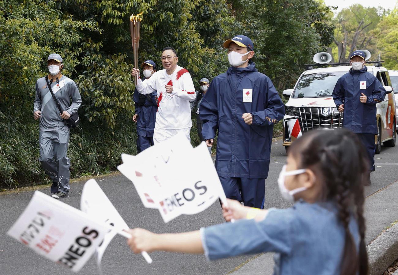 大阪府吹田市の万博記念公園で行われた聖火リレー。並走する関係者はマスクを着用した(共同)