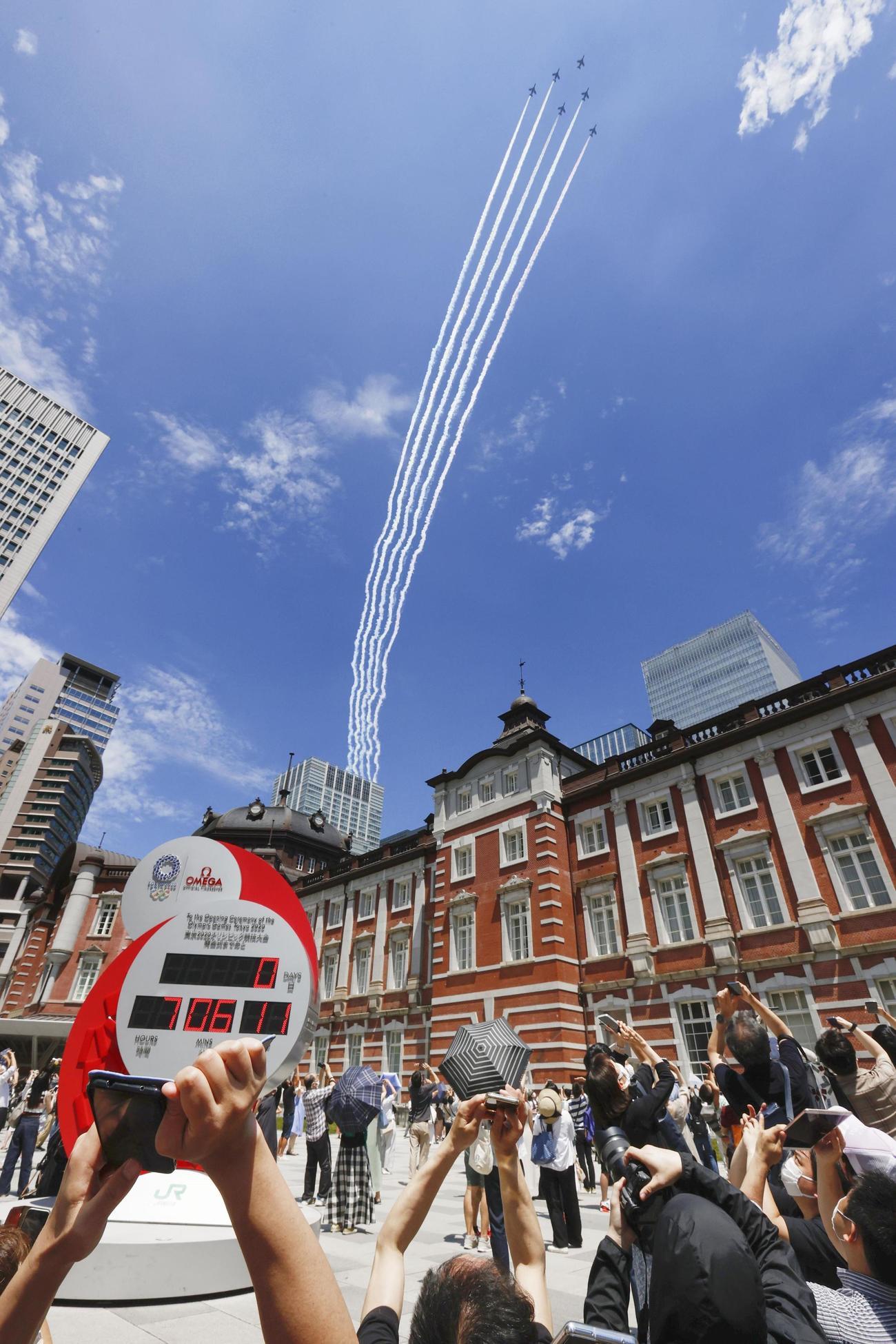 JR東京駅の上空を飛行する航空自衛隊の「ブルーインパルス」=23日午後0時53分(共同)