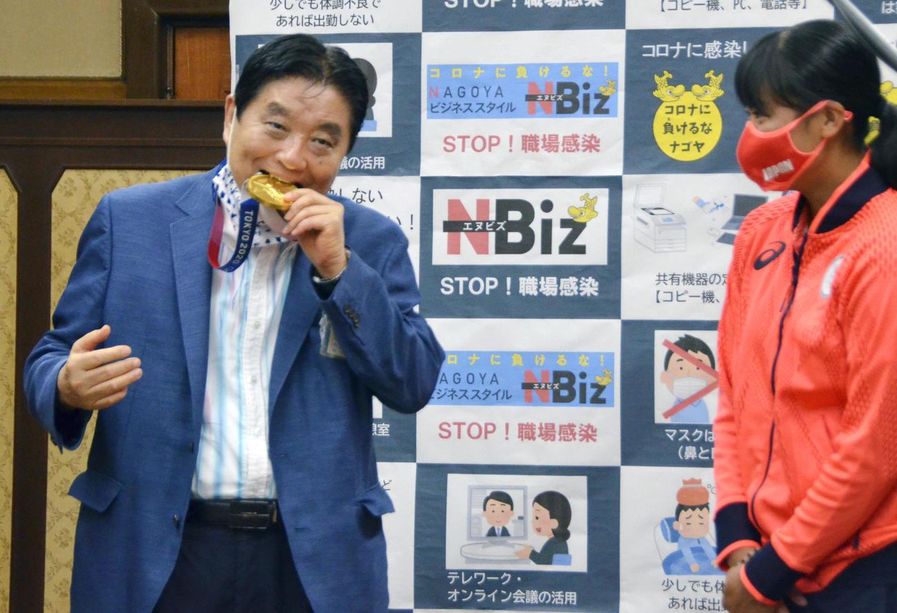 首に掛けられた後藤希友(右)の金メダルをかじる河村たかし名古屋市長
