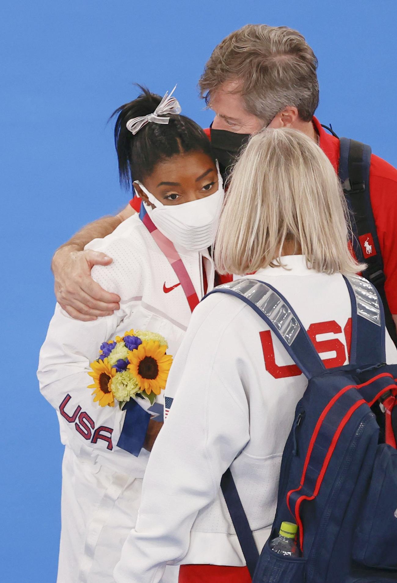 表彰式後、関係者に肩を抱かれるシモーン・バイルス(左)(共同)