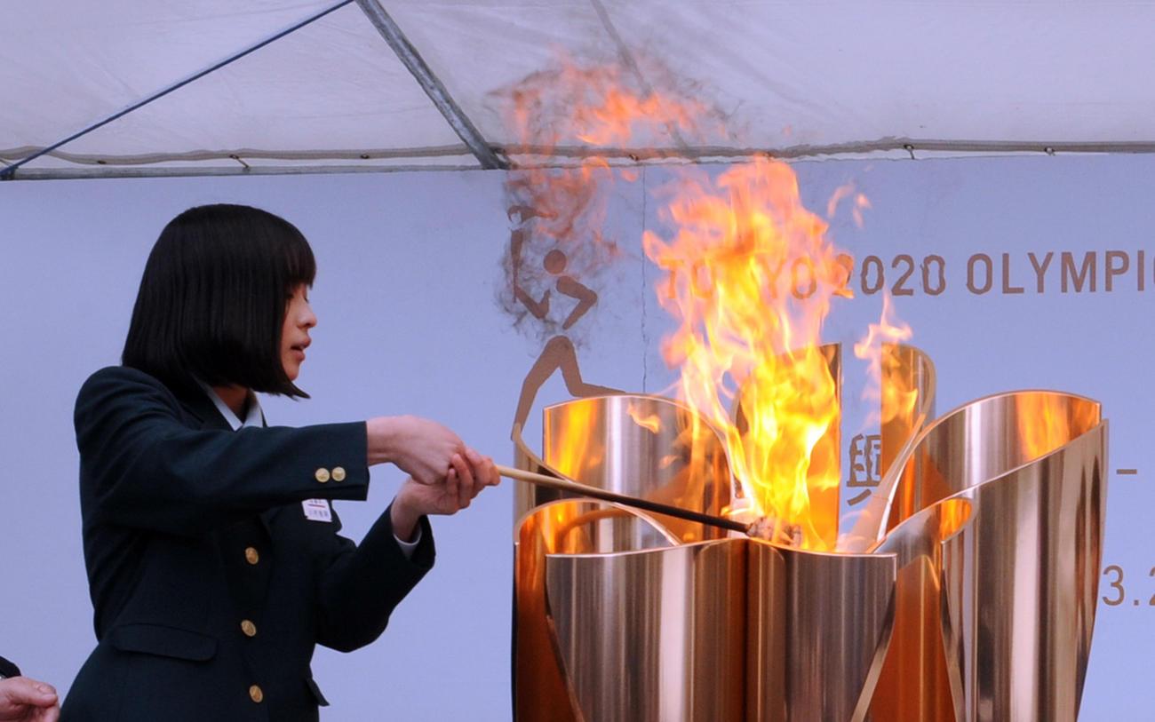 24日、東日本大震災で被災した川村桃明さんが聖火皿に「復興の火」をともす