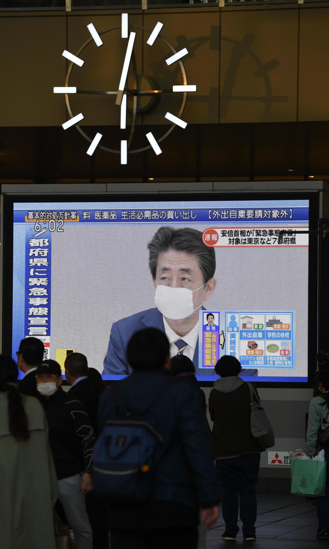 安倍首相の緊急事態宣言発令を伝えるニュースを足を止めてみる人々(撮影・前岡正明)