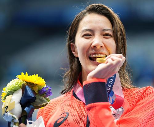 女子400メートル個人メドレー決勝 優勝した大橋は金メダルをかじる(撮影・鈴木みどり)