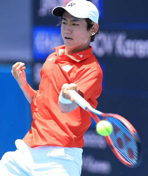 男子テニスシングルス1回戦、力強いショットを放つ西岡(撮影・河野匠)