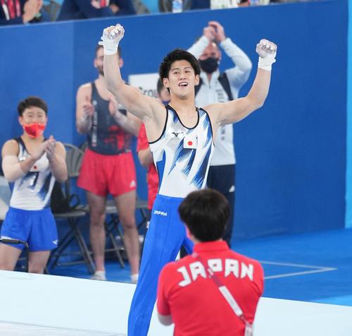 体操男子個人総合決勝で最後の演技の鉄棒を終え、ガッツポーズを見せる橋本大輝。左端は北園