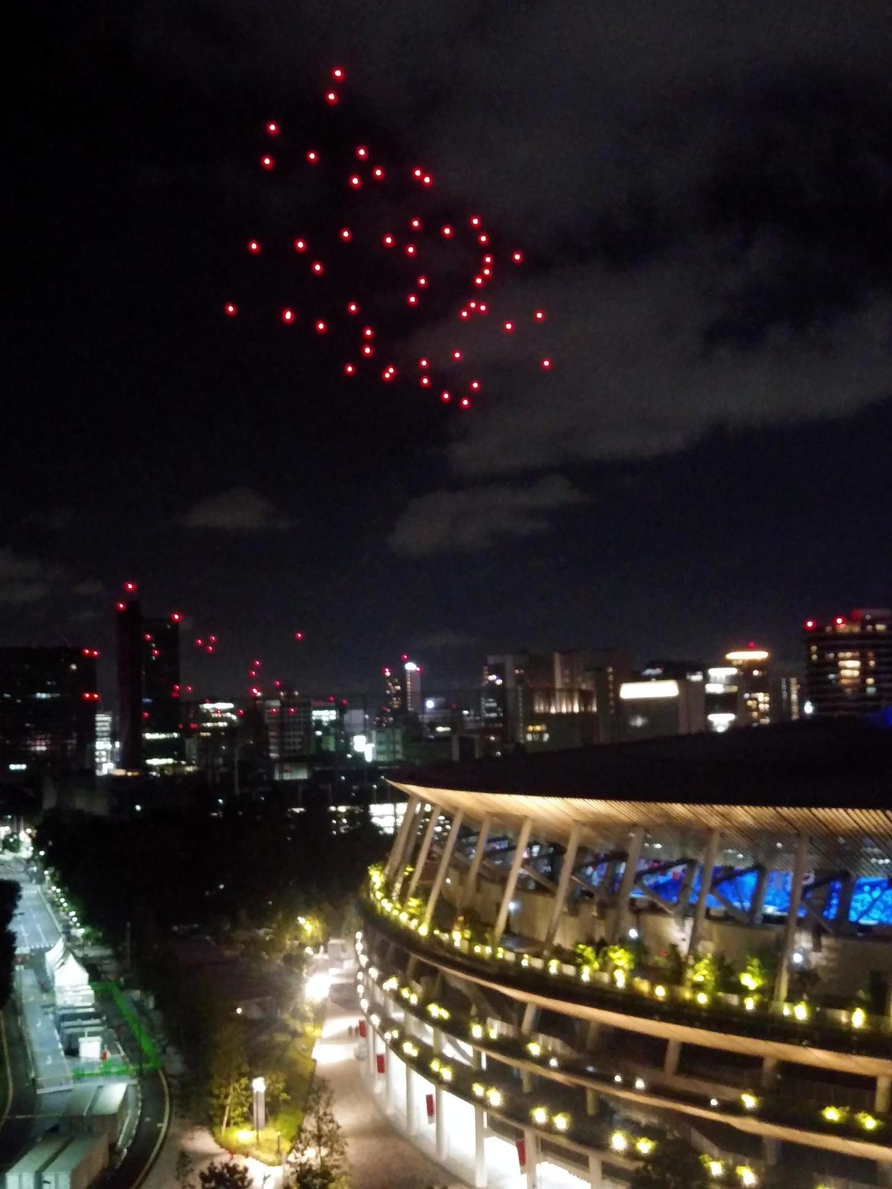 7月16日、国立競技場の上空に光り輝くドローンの集合体が立方体から徐々に形を変える(撮影・三須一紀)