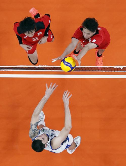 日本―イタリア 第1セット、ボールを押し込む高梨(右上)。同左は小野寺(共同)