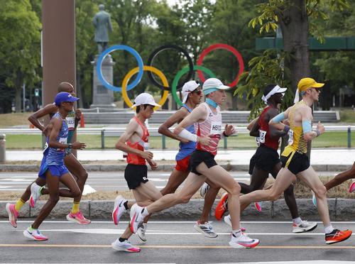 レース序盤、五輪マークのモニュメント前を力走する中村匠吾(中央左)(共同)