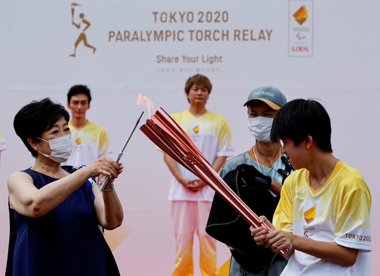 聖火に火を灯す小池百合子東京都知事(左)(ロイター)