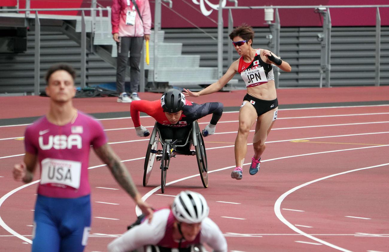 混合400メートルユニバーサルリレー(視覚障害、義足・機能障害、脳性まひ、車いす)予選で3走高松(右)は鈴木にタッチする(撮影・滝沢徹郎)