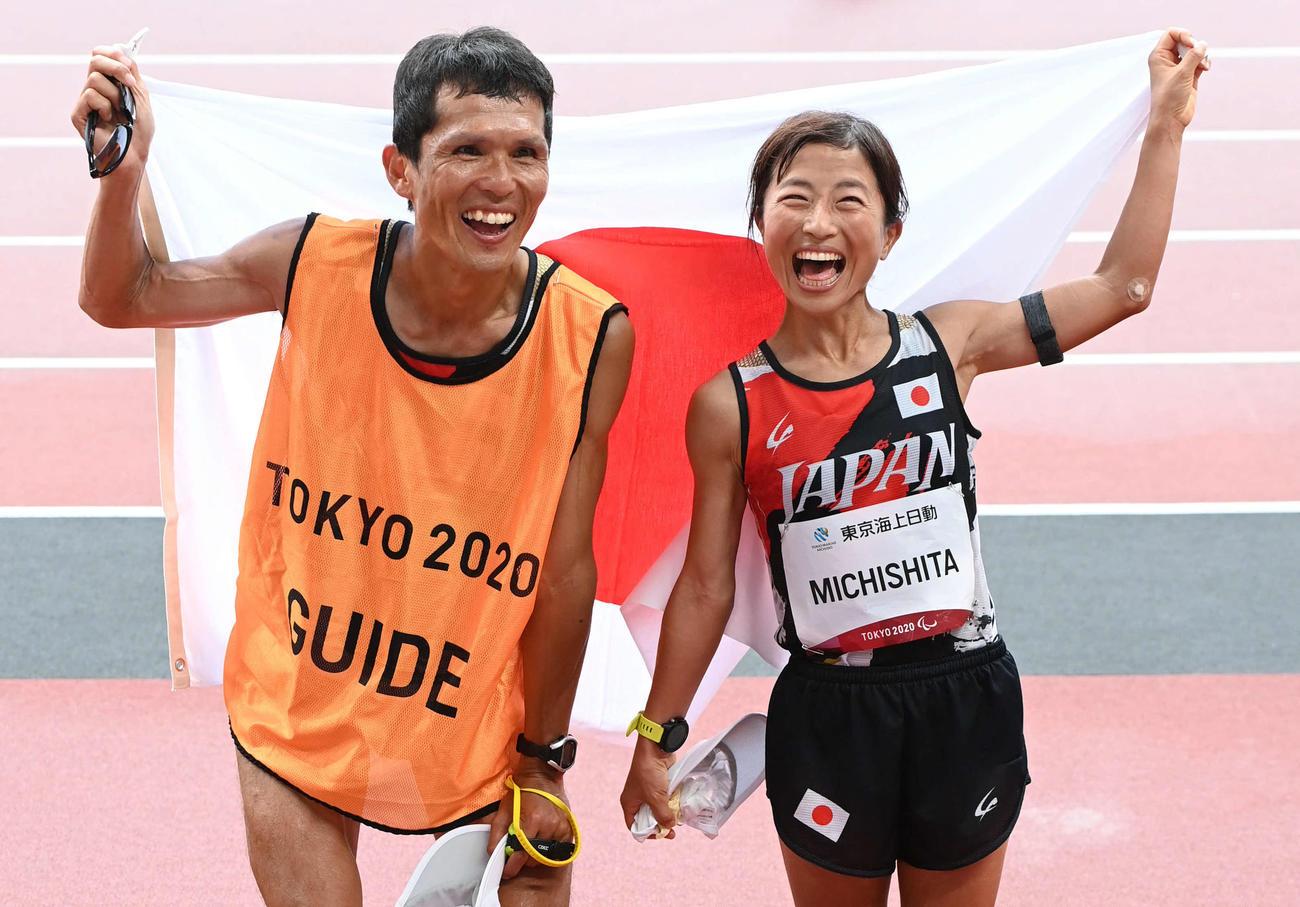 女子マラソン(視覚障害T12)金メダル獲得の道下(右)は伴走者の志田淳と笑顔を見せる=(撮影・山崎安昭)