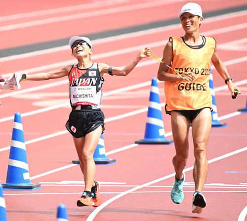 女子マラソン(視覚障害T12) 金メダル獲得の道下は伴走者の志田宗と笑顔を見せる(撮影・山崎安昭)