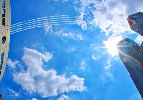 カラースモークで東京上空を飛行するブルーインパルス(撮影・河田真司)