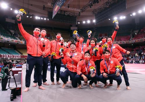 混合団体で銀メダルを獲得し記念撮影に臨む日本の選手たち。左からウルフ、原沢、永瀬、素根、向、新井、大野将平、芳田、田代、浜田、阿部一、阿部詩(撮影・パオロ ヌッチ)