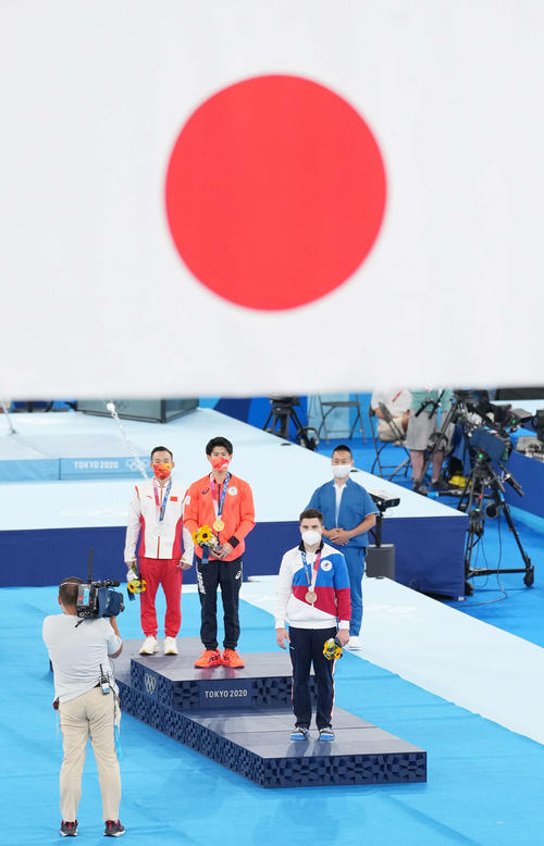 体操男子個人総合で金メダルを獲得し、表彰台のてっぺんで日の丸を見つめる橋本(中央)