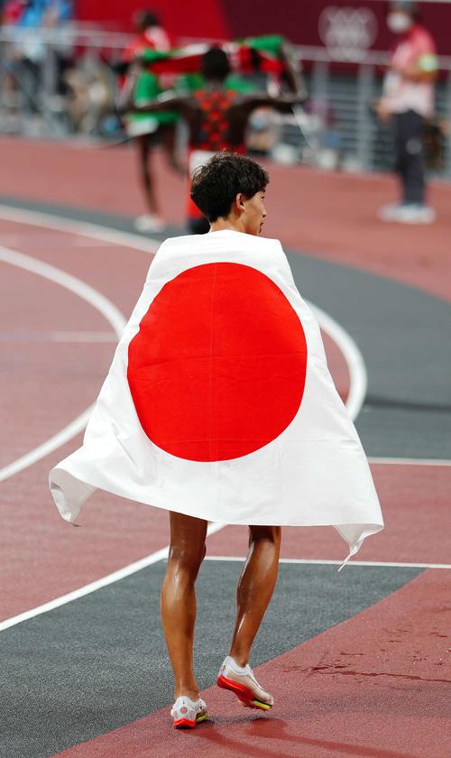 男子3000メートル障害決勝 7位入賞し日の丸を背中にかける三浦(撮影・江口和貴)