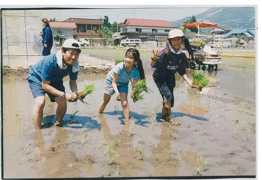 福島県での宿泊学習で田植え体験をする、小学5年生の岩渕真奈(右)。左が河村秀樹先生