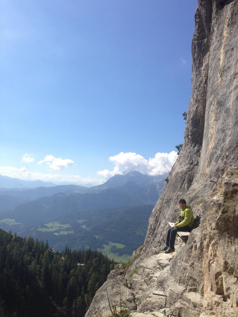 オーストリア・アイスリーゼンベルト入口の板に座り、アルプスの山々を眺める杉本怜(本人提供)