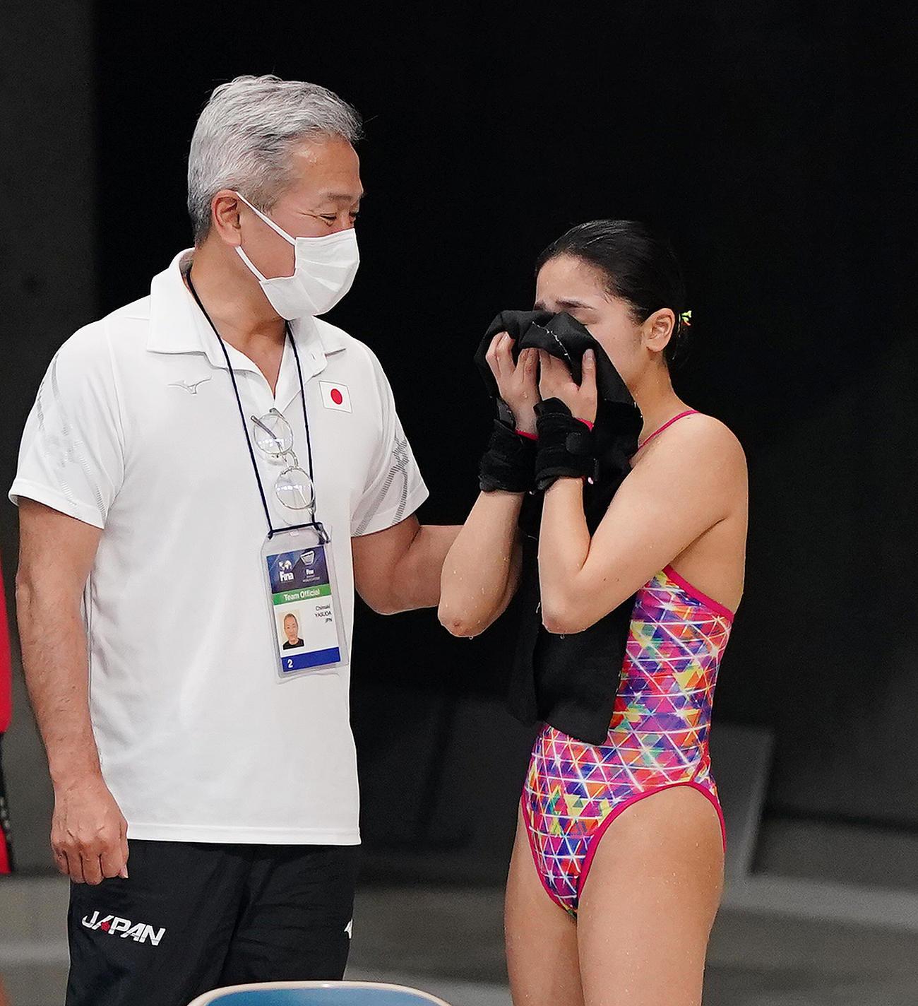 女子高飛び込み予選で24位に終わり、安田千万樹コーチ(左)に声をかけられ目頭を押さえる安田舞(撮影・菅敏)