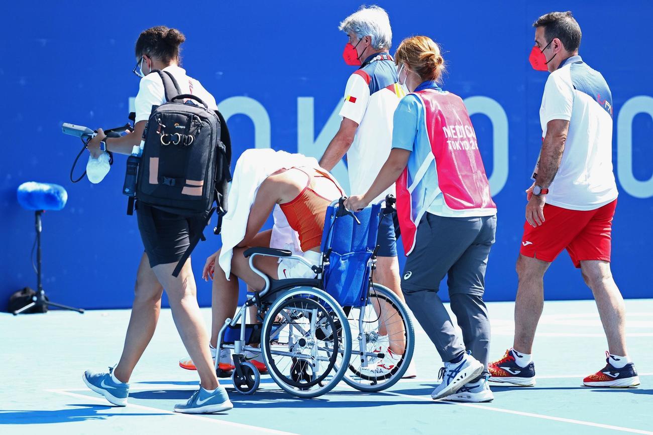 テニス女子シングルス準々決勝 車いすでコートから運び出されるバドサ(ロイター)