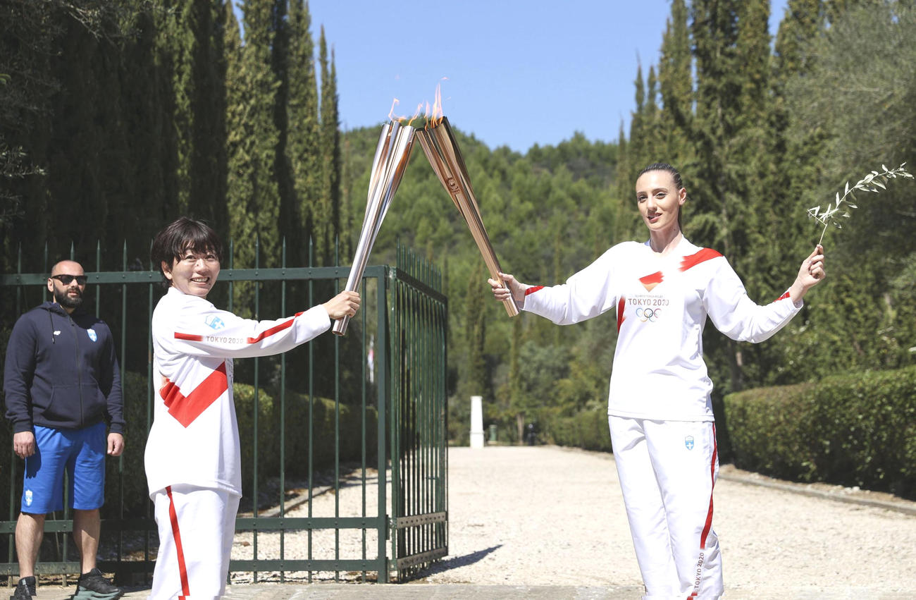 ギリシャのオリンピア遺跡で行われた東京五輪の聖火リレーで、第1走者のアナ・コラカキ選手(右)から聖火を引き継ぐ野口みずきさん(共同)