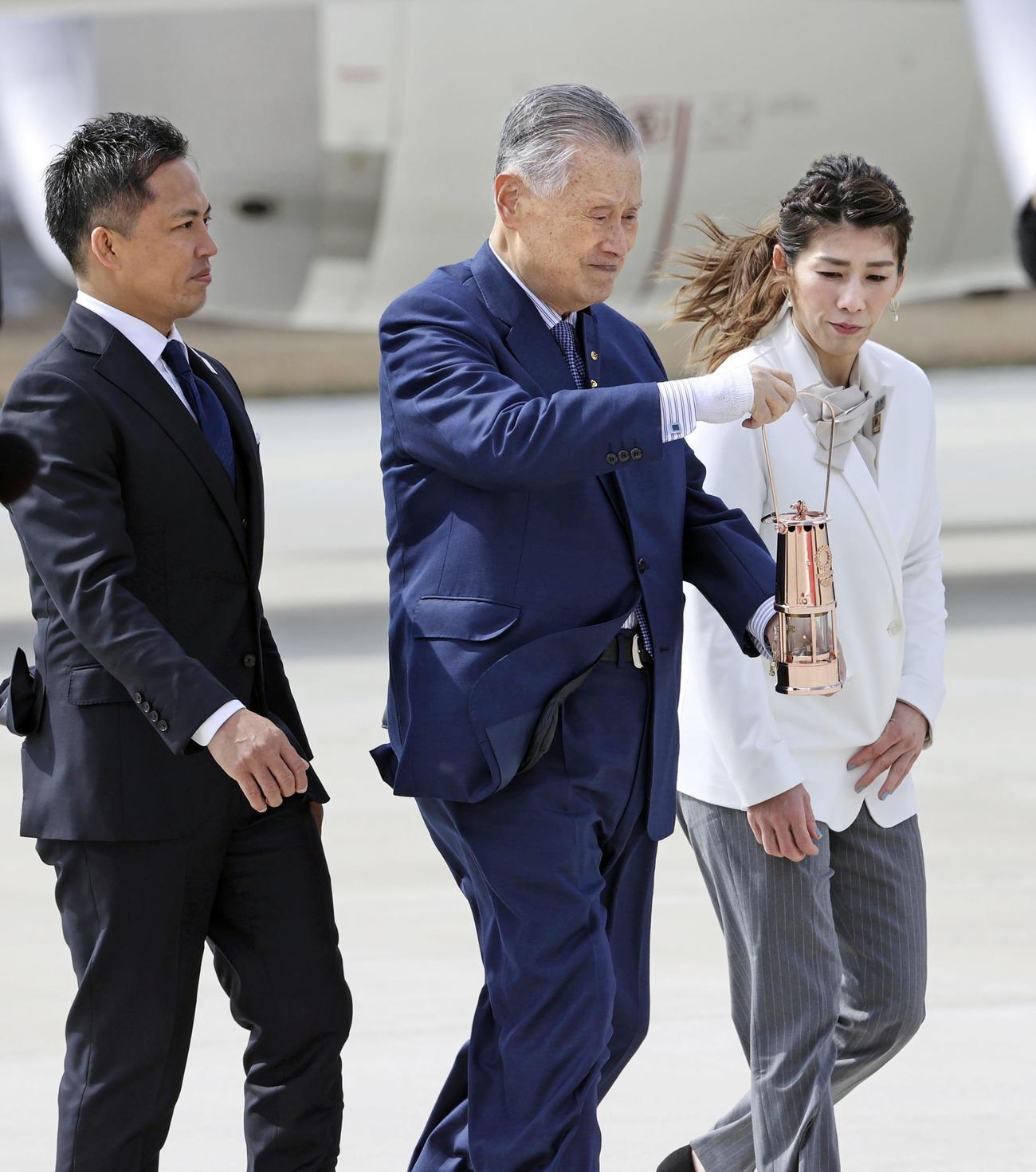 特別輸送機で到着した東京五輪の聖火を運ぶ組織委の森喜朗会長(中央)。左は柔道男子の野村忠宏さん、右はレスリング女子の吉田沙保里さん(共同)