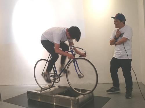 安部賢一(左)はローラーで自転車をこぎ、時速64キロを記録。主人公を演じた脚力を披露し会場はどよめく。若いころは競輪選手を目指した(18年5月18日撮影)