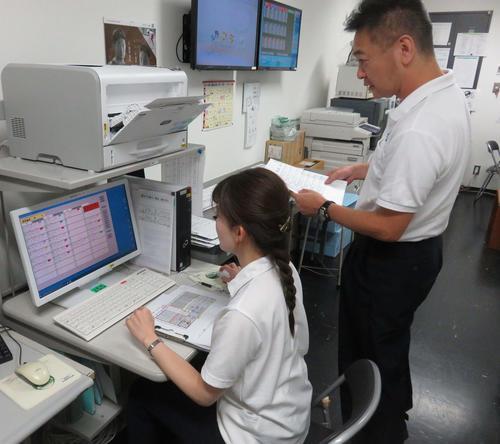戸田さん(左)が岩田課長とともに仮番組をつくる。モニター上で、競走得点や直近成績などが記された選手データを各レースに振り分ける