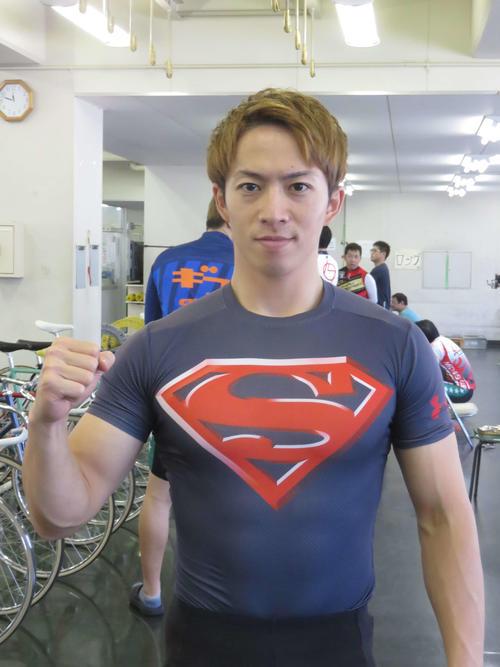 スーパーマンTシャツを着てガッツポーズを見せる坂井洋