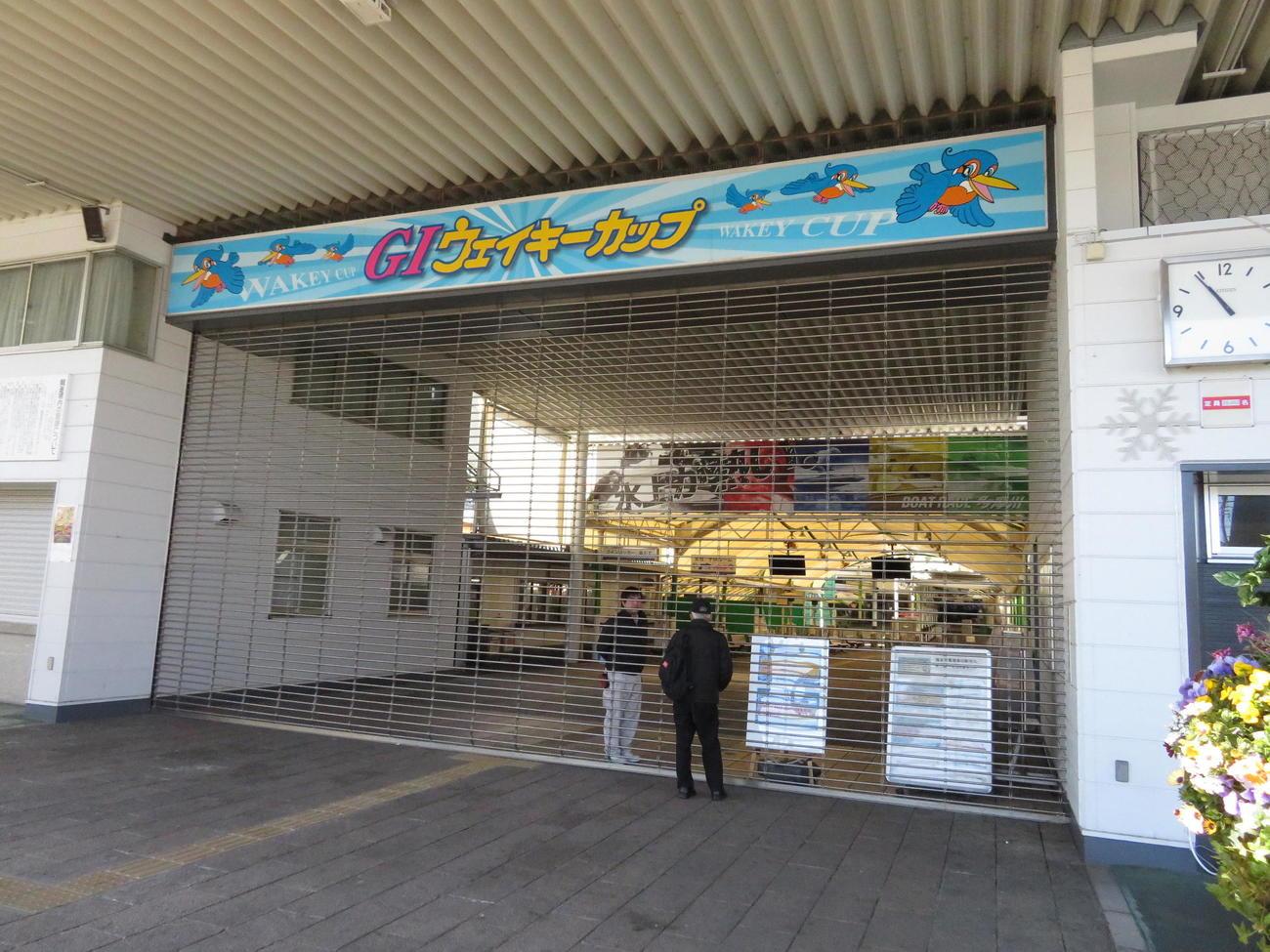 閉鎖された多摩川ボートの正門でファンに説明する関係者