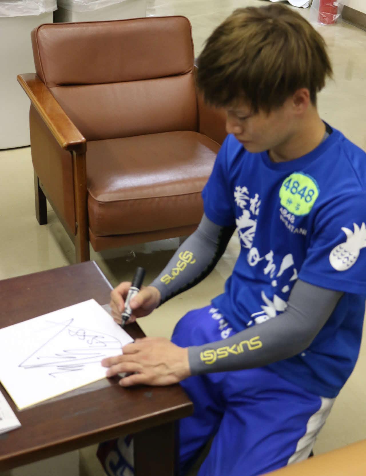 逃げて今年2度目の優勝を飾った仲谷颯仁が色紙にサインをする