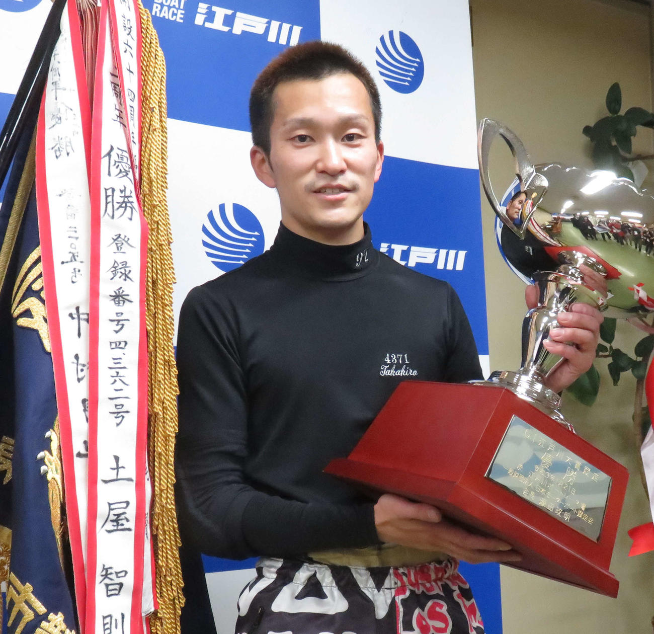 優勝カップを手にして笑顔を見せる西山貴浩