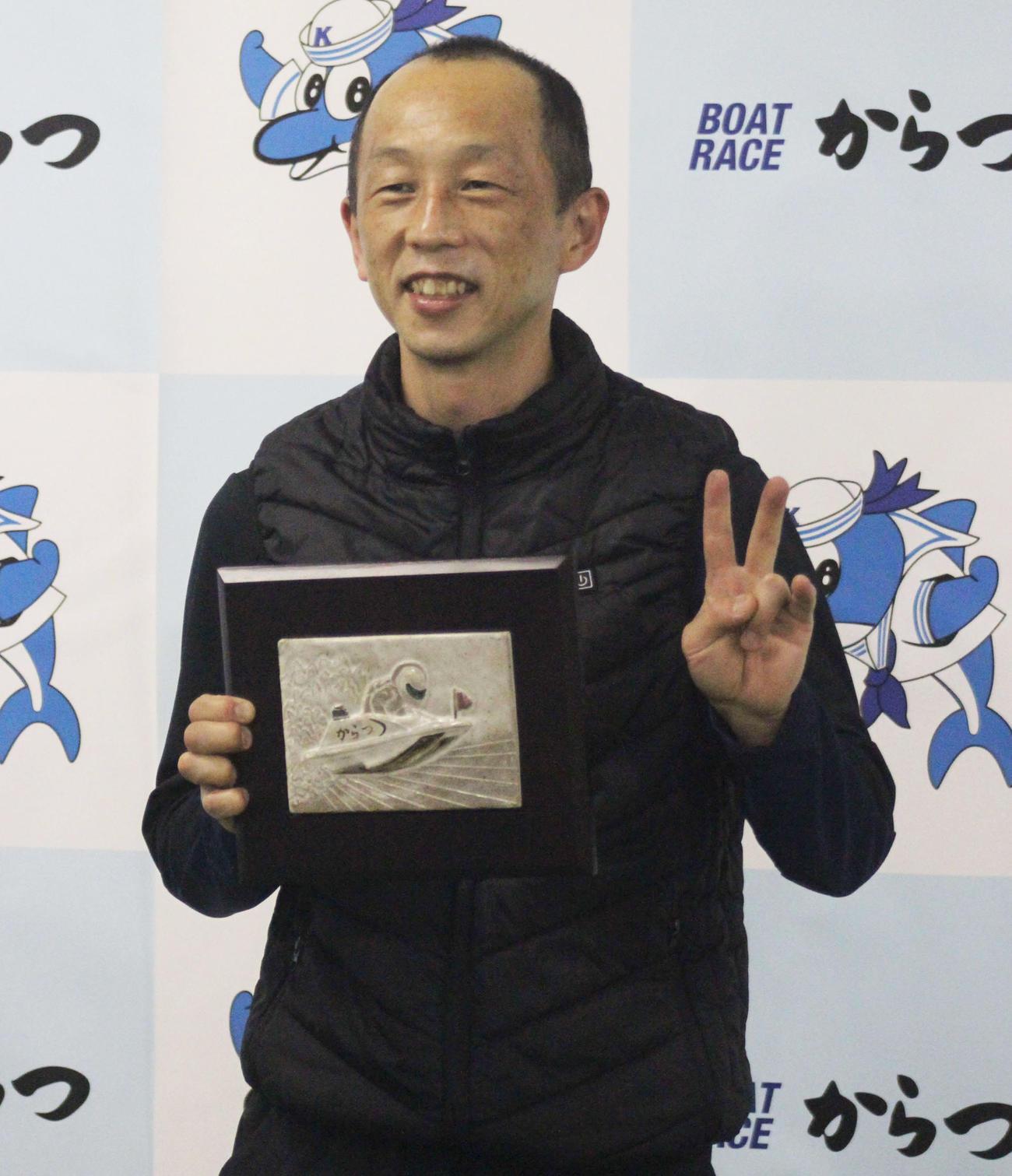 通算2000勝を達成した安田政彦は、記念盾を手に笑顔を見せた