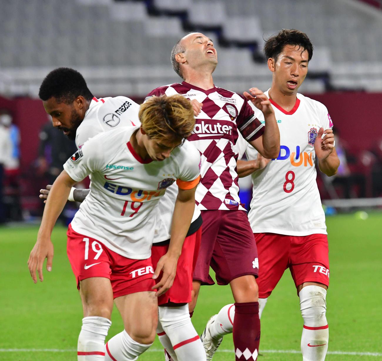 4日、神戸MFイニエスタ(中央)のシュートを阻む広島の選手たち
